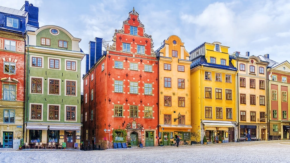Seven colorful buildings along a cobblestone street on a sunny day in Stockholm, Sweden