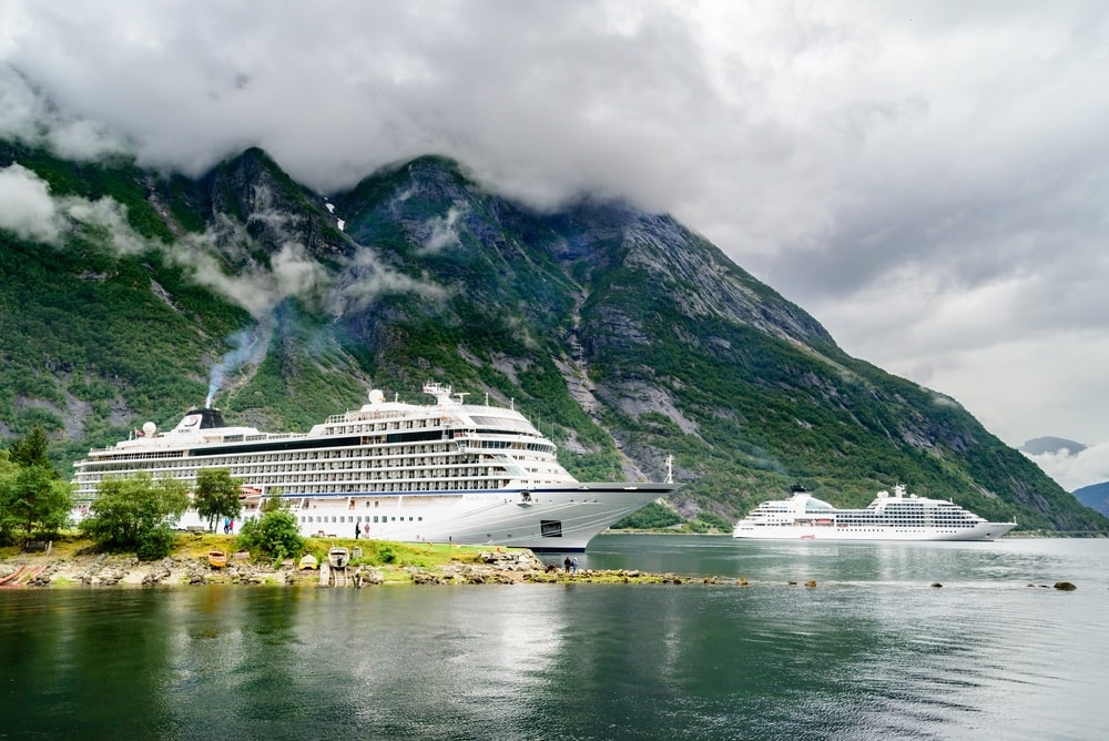 Travel documentary of the luxury cruise ships Viking Star and Seaborn Quest moored in fjord. High and steep mountainside in background with rainclouds in the sky.