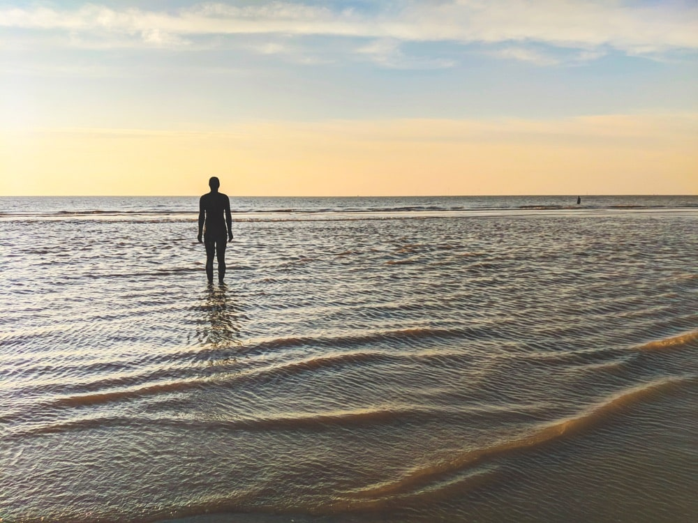 About one hundred of these cast iron statues face the sea in Sir Antony Gormley's Another Place at Crosby Beach, Lancashire. | Photo by Eddie Jordan Photos / Shutterstock