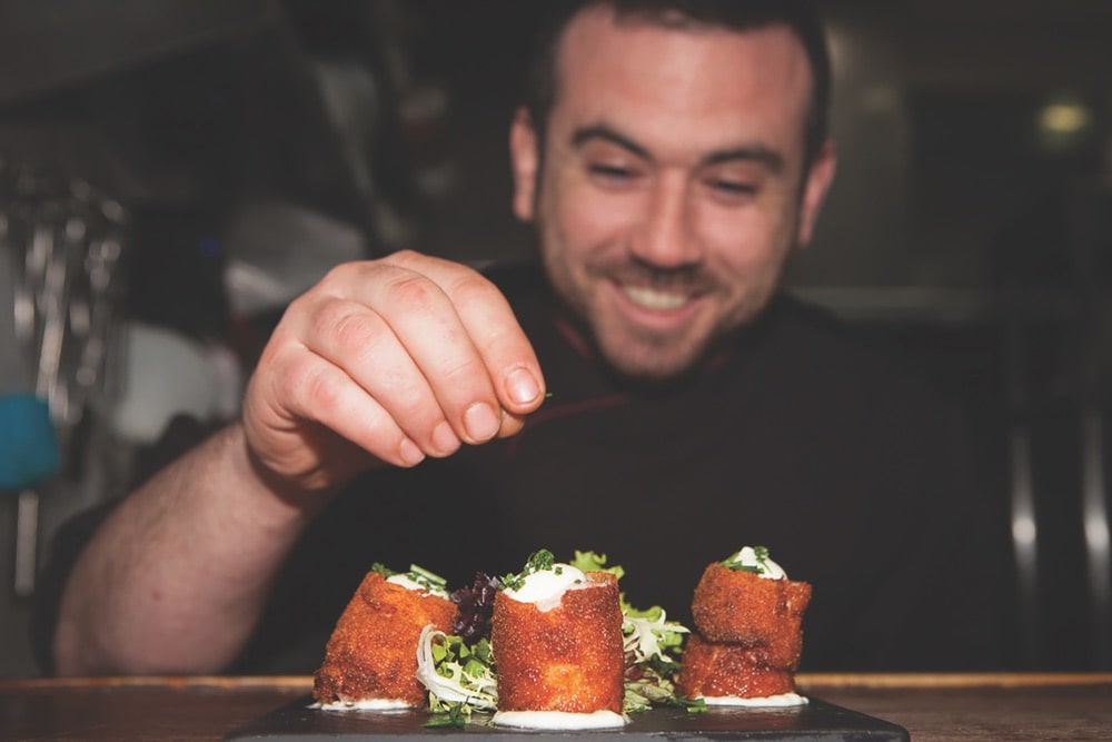 Chef Fernando of Toma and Coe food tours puts the final touch on some Spanish tapas.