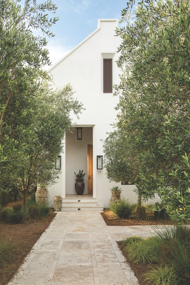 Olive trees line the entry sequence into the Cape Dutch–influenced Finley residence in Inlet Beach, Florida, A Boheme Design, A Boheme