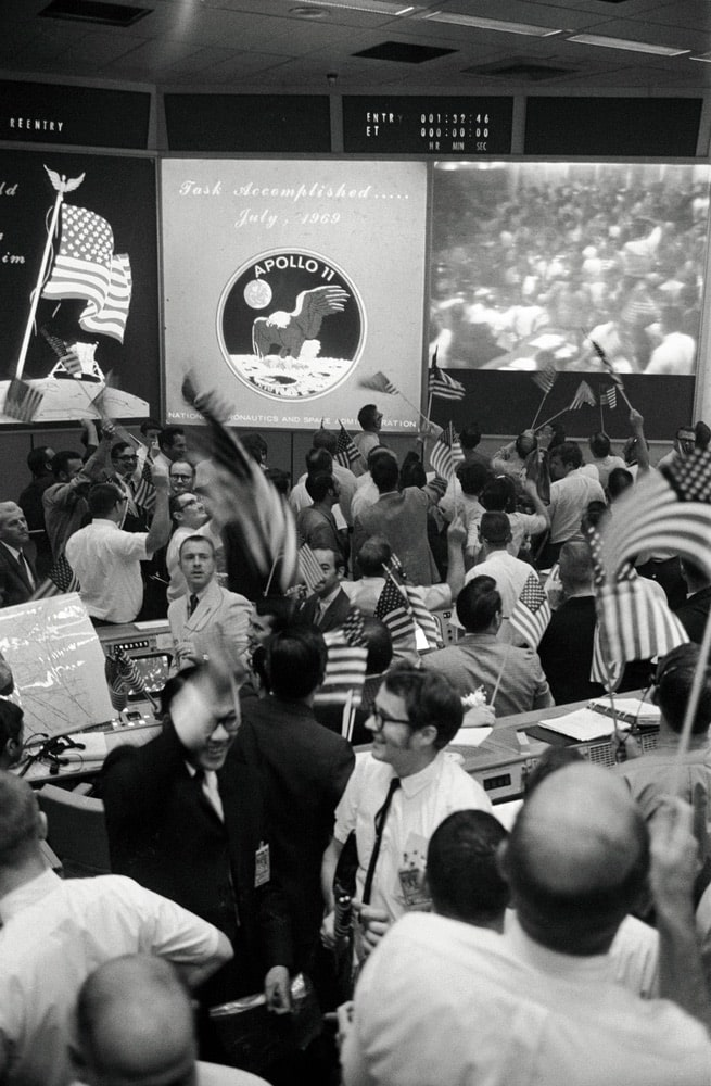 Overall view of the Mission Operations Control Room (MOCR) in the Mission Control Center (MCC), Building 30, Manned Spacecraft Center (MSC), showing the flight controllers celebrating the successful conclusion of the Apollo 11 lunar landing mission. nasa, apollo 11 50th anniversary