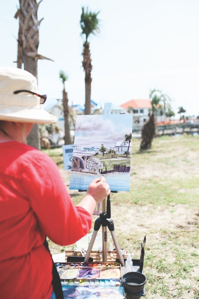 Artist Brienne M. Brown of Julian, Pennsylvania, paints near the welcome center in Mexico Beach, Florida, during the 2019 Forgotten Coast en Plein Air event.