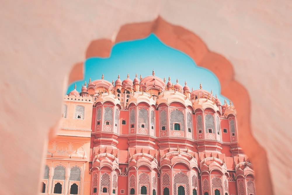 Hawa Mahal—the Palace of Winds—lies on the edge of Jaipur's City Palace. Its many-windowed facade was originally designed not only to allow air to flow more freely into the rooms, but also to enable the ladies of the palace to look out upon the streets and activities below without being seen. Red and pink sandstone give the rosy hue to the area's buildings, earning Jaipur its modern nickname, the Pink City.