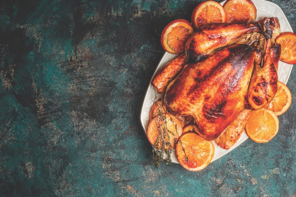 Roast whole turkey or chicken in plate with roasted oranges on dark rustic background, top view, Suzanne Pollak Column August 2018 Architecture and Design Issue