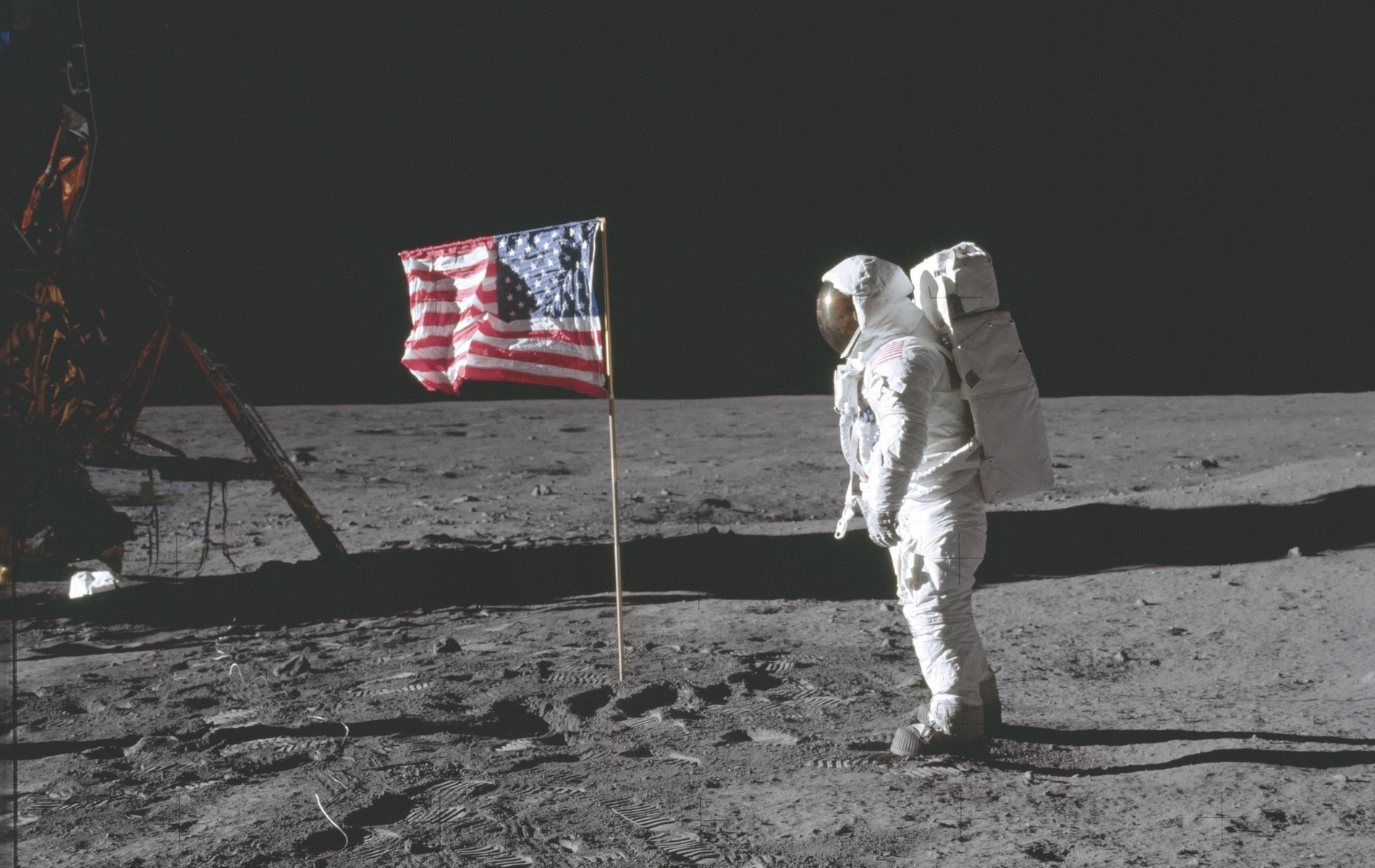 Buzz Aldrin poses beside the deployed United States flag during Apollo 11 extravehicular activity on the lunar surface. The lunar module (LM) is on the left, and the footprints of the astronauts are visible in the soil of the moon. Neil Armstrong took this photo with a 70mm Hasselblad lunar surface camera. While Armstrong and Aldrin descended in the Eagle LM to explore the moon's Sea of Tranquility region, Michael Collins remained with the command and service module Columbia in lunar orbit. NASA