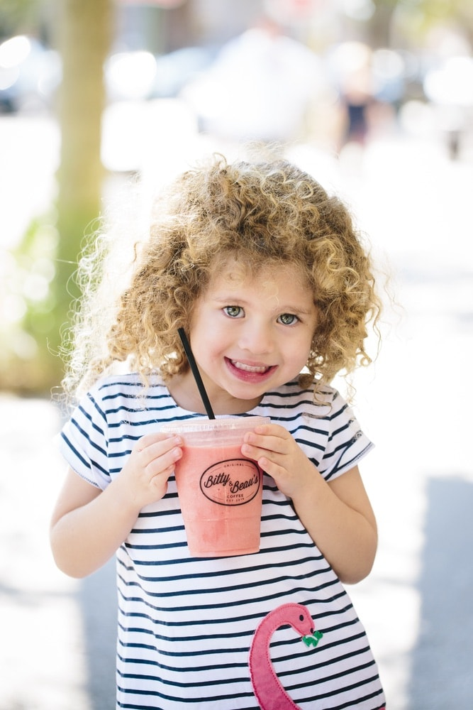 A little girl enjoying a pink smoothie from Bitty & Beau's Coffee's Charleston location