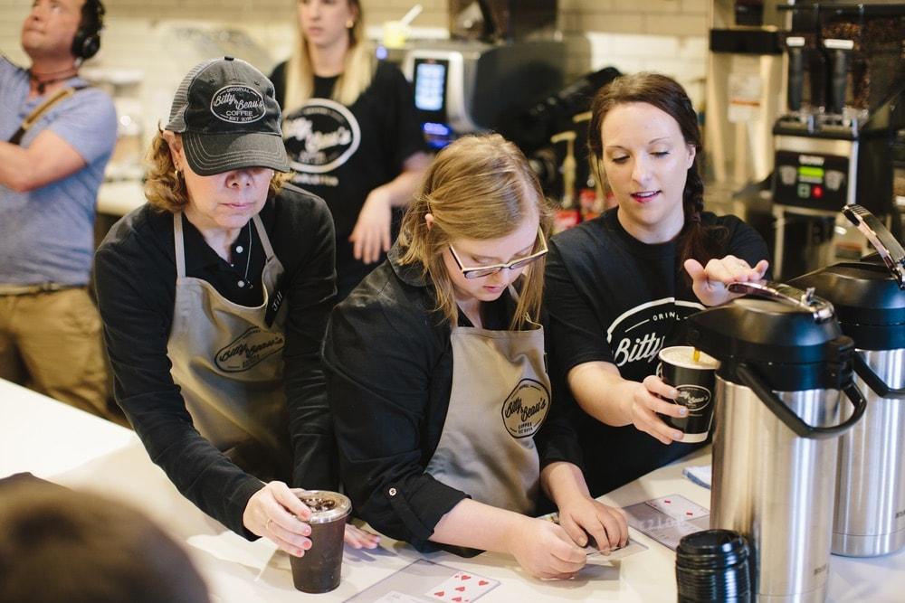 Three employees preparing coffee orders at Bitty & Beau's Charleston location.