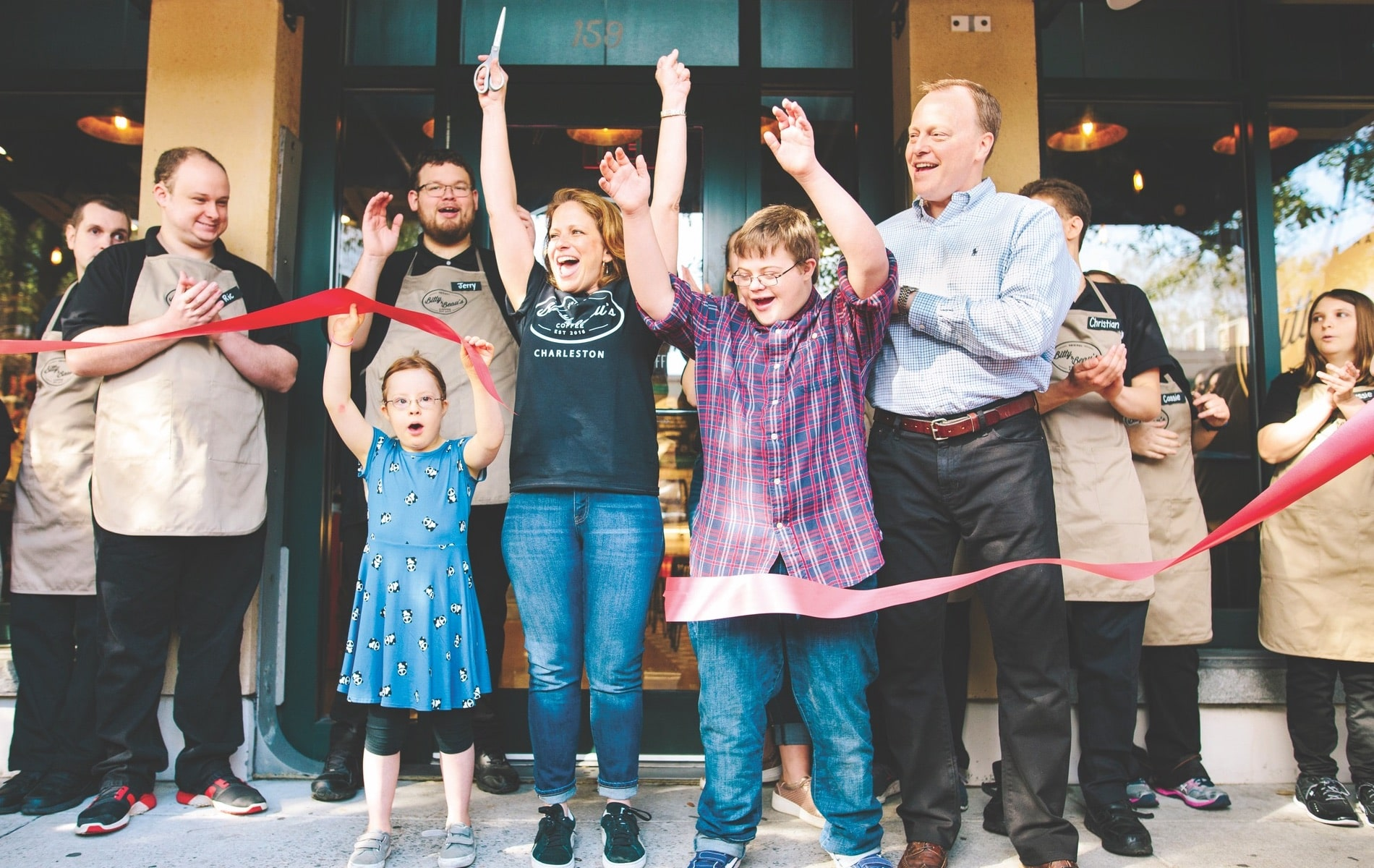 Wright family with a few employees standing on the sidewalk outside of the coffee shop at the Grand Opening for Bitty & Beau's Charleston location