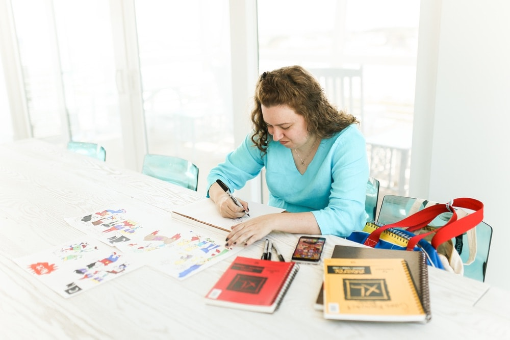 Camille Butchikas drawing cartoon-style artwork in her home in Northwest Florida using markers.