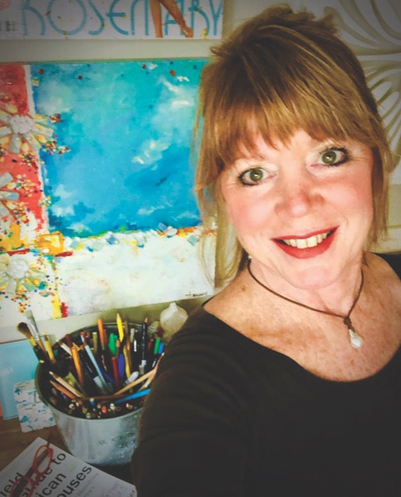 """Artist Tamera """"Tammy"""" Massey taking a selfie in front of her artwork and art supplies"""