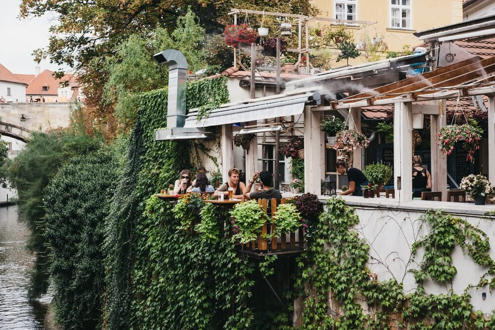 People drinking beer at the outdoor tables of Velkopřevorský Mlýn restaurant in Malá Strana, Prague