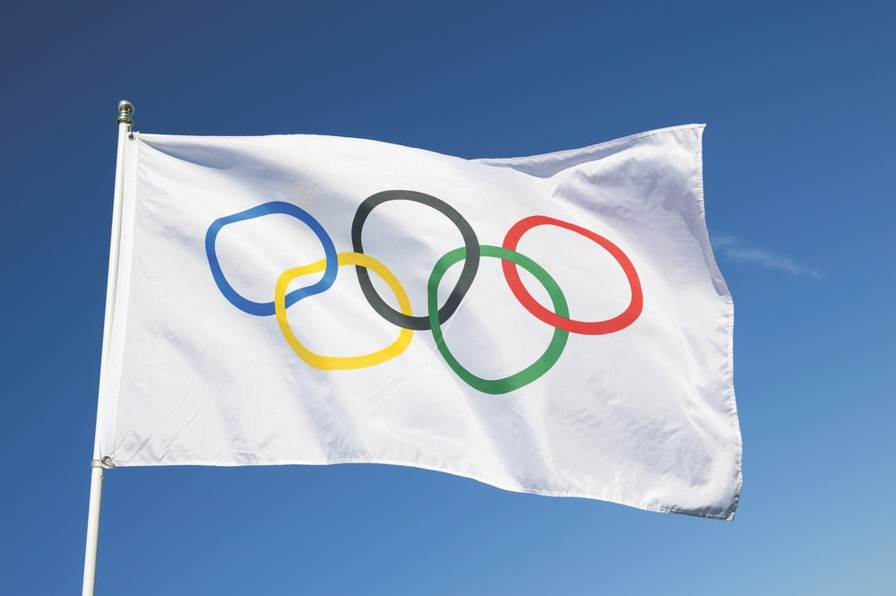 An Olympic flag flutters in the wind against bright blue sky in celebration of the city hosting the Summer Games