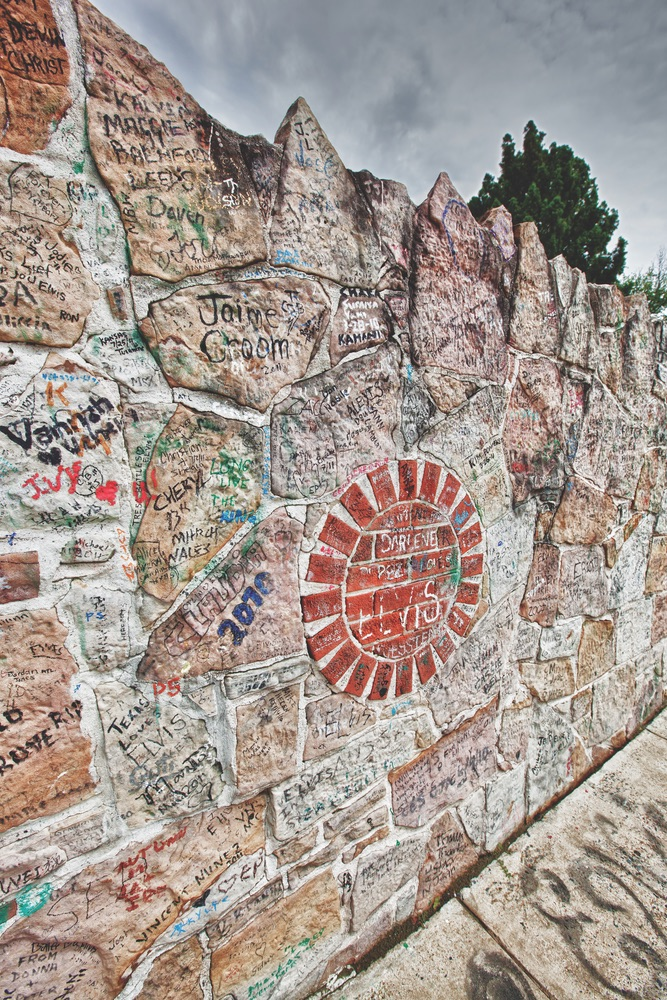 The wall surrounding Graceland Mansion. Here, hundreds of thousands of fans have written messages to Elvis over the years