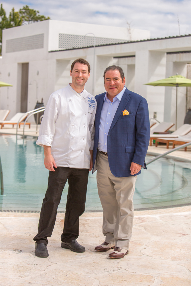 Chef Kevin Korman of Caliza Restaurant in Alys Beach poses with Emeril by Caliza Pool. Photo by Romona Robbins. VIE Magazines in depth look at Emeril and Alden Lagasse, A Bountiful Life.