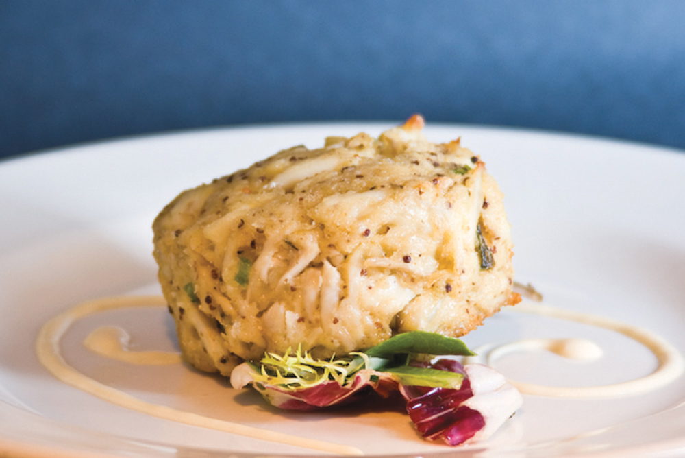 Café Thirty-A's Jumbo Lump Crab Cake Recipe Serves 8 as an appetizer or 4 as an entrée  2 pounds jumbo lump crabmeat, cartilage removed 3/4 cup thick mayonnaise 1/4 cup sour cream 2 tablespoons whole grain mustard 1 large egg, lightly beaten 4 tablespoons chopped scallions 1 teaspoon Old Bay Seasoning 1/4 teaspoon salt Preheat oven to 400 degrees. Spray baking sheet with Pam. Whisk together mayonnaise, sour cream, mustard, and egg in mixing bowl until combined well. Gently fold in crab and other ingredients with a rubber spatula until just combined. Gently form mixture into eight 1-inch-thick cakes and transfer to baking sheet. Bake for 15 minutes, or until lightly golden. Run a spatula under them once or twice to make sure they're not sticking. When the cakes are ready, place them under a preheated broiler for two to three minutes, or until lightly browned on top. Remove from broiler and let stand on baking sheet for five minutes. Serve with lemon wedges, salad greens, and sauce of choice.