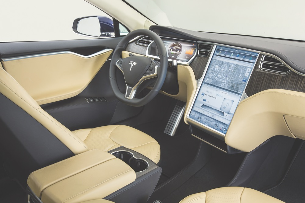 The sleek and luxurious interior of the Model S features supple leather, exotic wood, and high-tech instrumentation, including an oversized touch screen interface in the center console