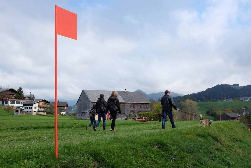 Visitors walk path of orange flags through pastures Werkraum Bregenzerwald Austria