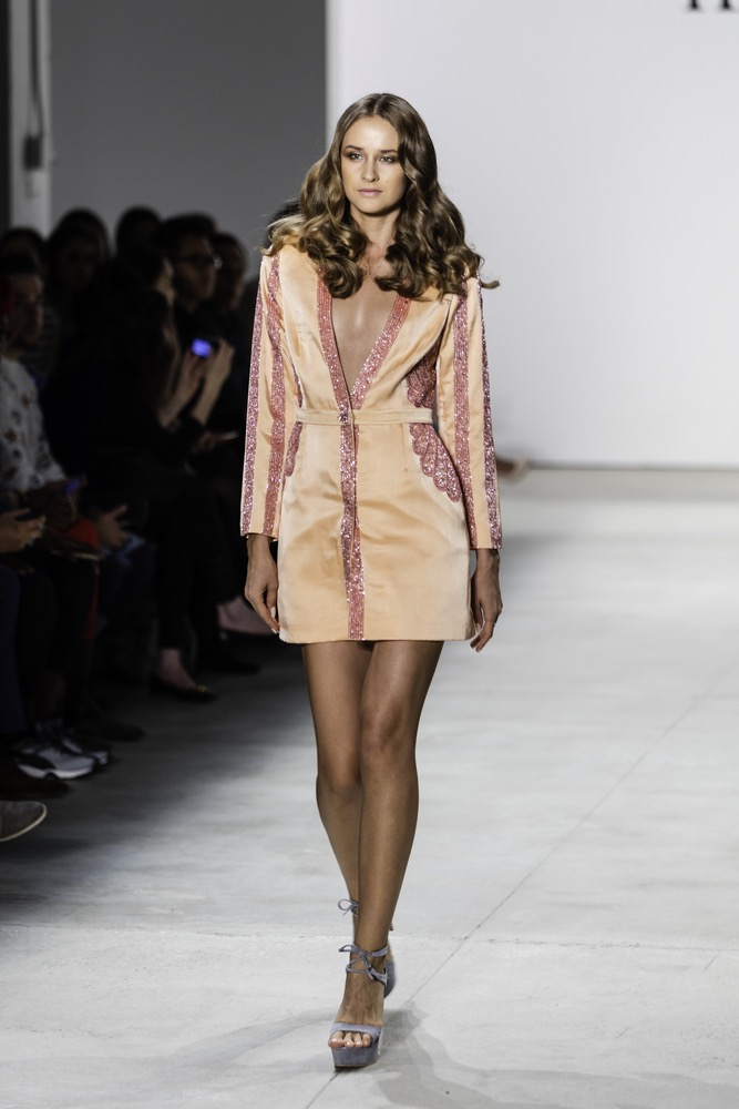 Model Walking Down New York Fashion Week Runway In A Sherbet Orange Deep V Shirt Dress With Rose Colored Trims
