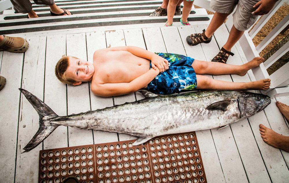 boy laying next to fish mexico beach florida fishing