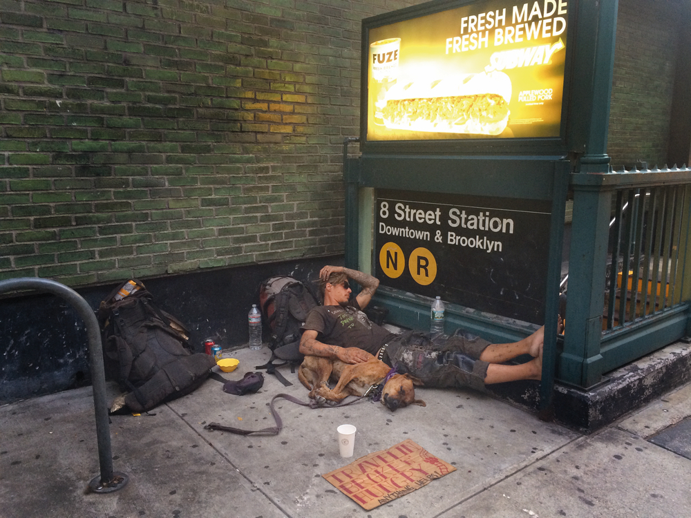 Homeless man and pet sleeping outside subway station