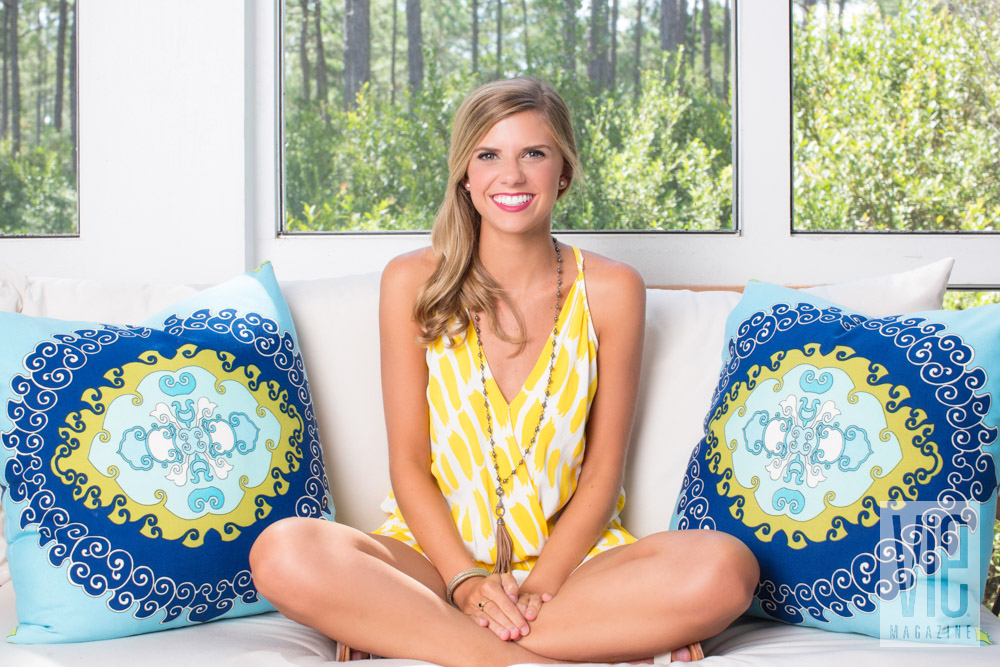 Lucy models a yellow dress with blue throw pillows