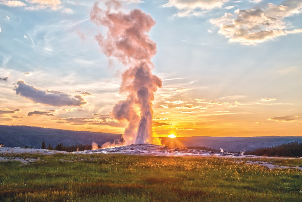 Old Faithful erupting at sunset in Yellowstone National Park—hold on to your cell phones, people!