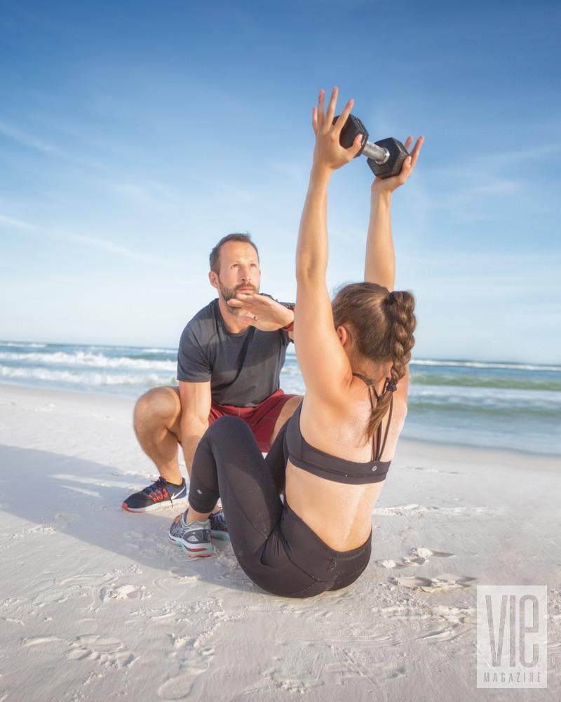 Zoli Nagy training girl on beach by lifting weights