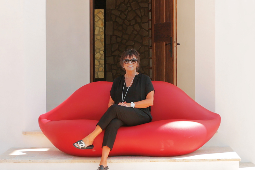 Linda Miller in front of one of her properties luxury real estate the smile of 30a lips sofa
