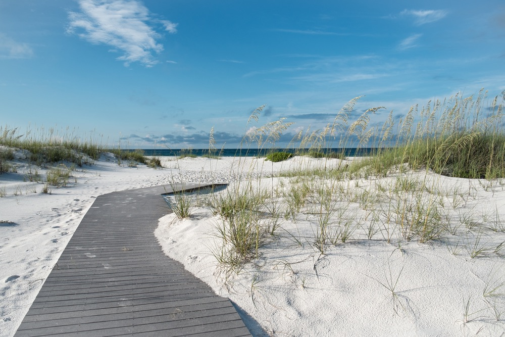 Small rustic boardwalk footpath through snow white sand dunes at a pristine Florida beach