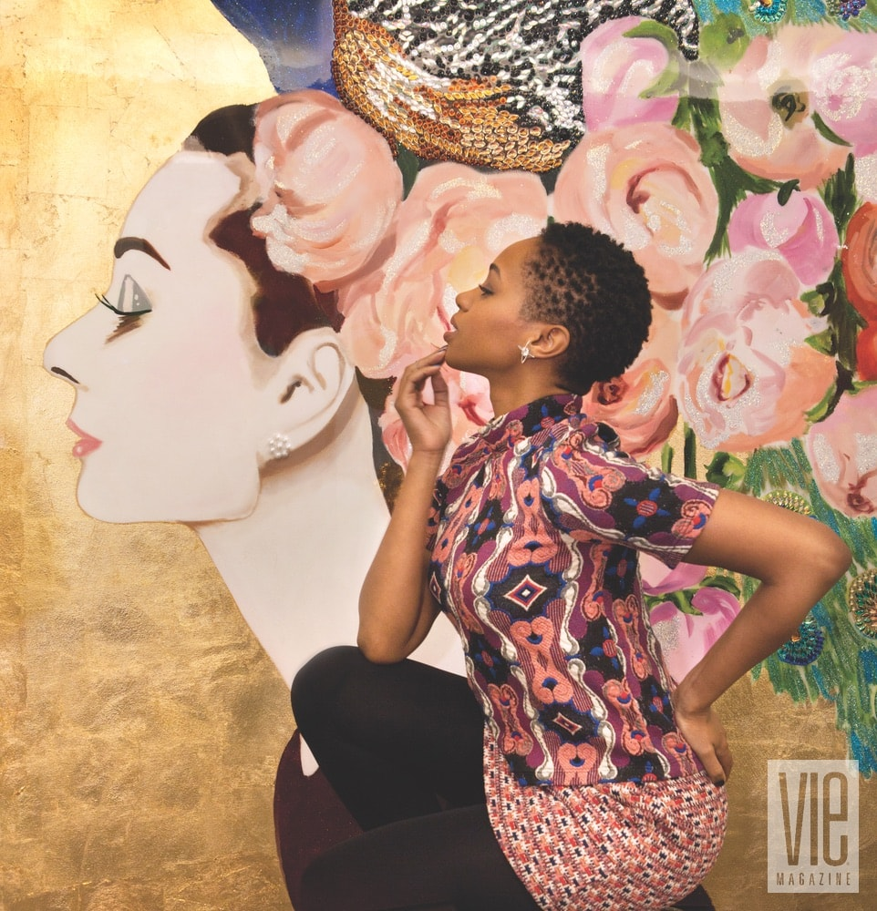 An attendee at the BG x Ashley Longshore opening event posing with a signature Audrey painting.
