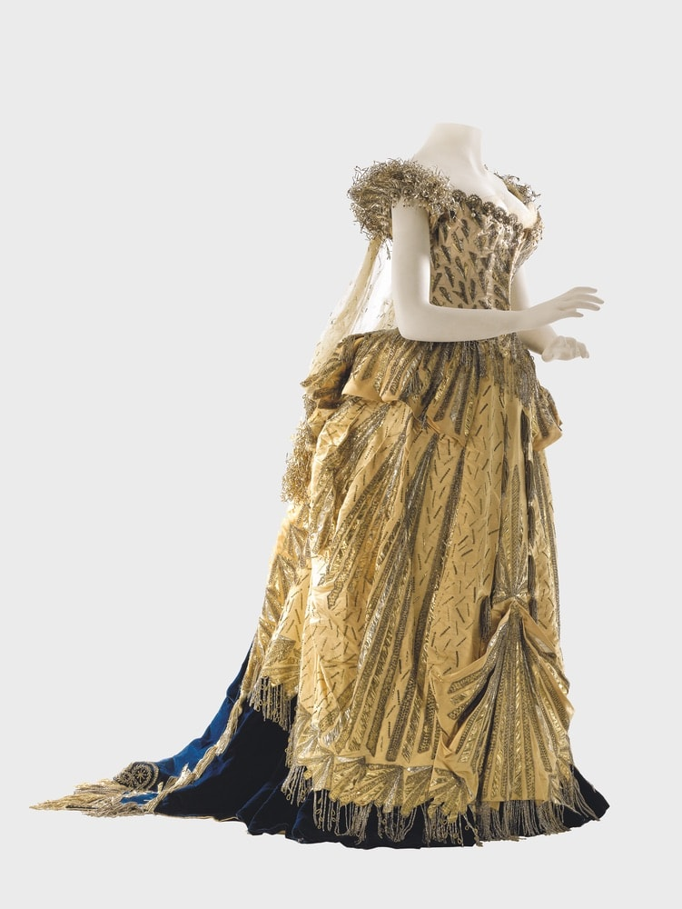 "The ""Spirit of Electricity"" costume made by Worth for Alice Vanderbilt, 1883. It comprises a dress of seventeenth-century inspiration in midnight-blue velvet, overlaid with white satin on the bodice and gold satin on the skirt, embroidered with sequins, beads, and crystals."