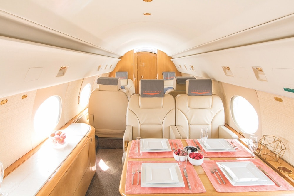 Inside of a JetSmarter jet with a table setting and fresh fruit.