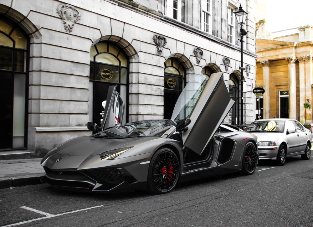 grey matte Lamborghini Aventador SV Roadster with both doors open is parked in Birmingham city centre. This effective hypercar is one of 500 cars of the model ever made