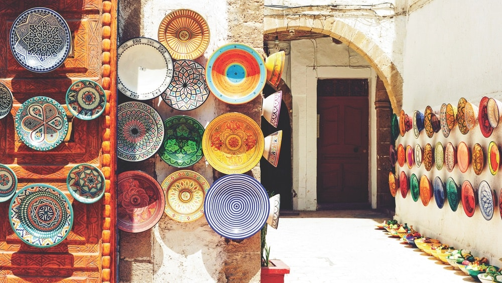Colorful handcrafted plates line a market stall in Marrakech, Morocco.