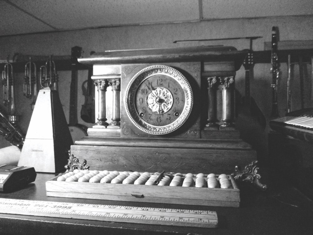 Seth Thomas Adamantine mantel clock sitting on a piano in black and white
