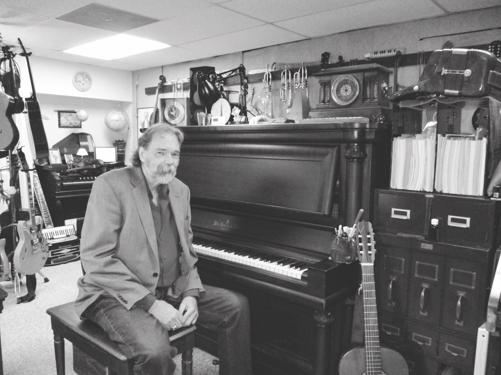 Reed sitting on a piano bench in front of his piano in black and white