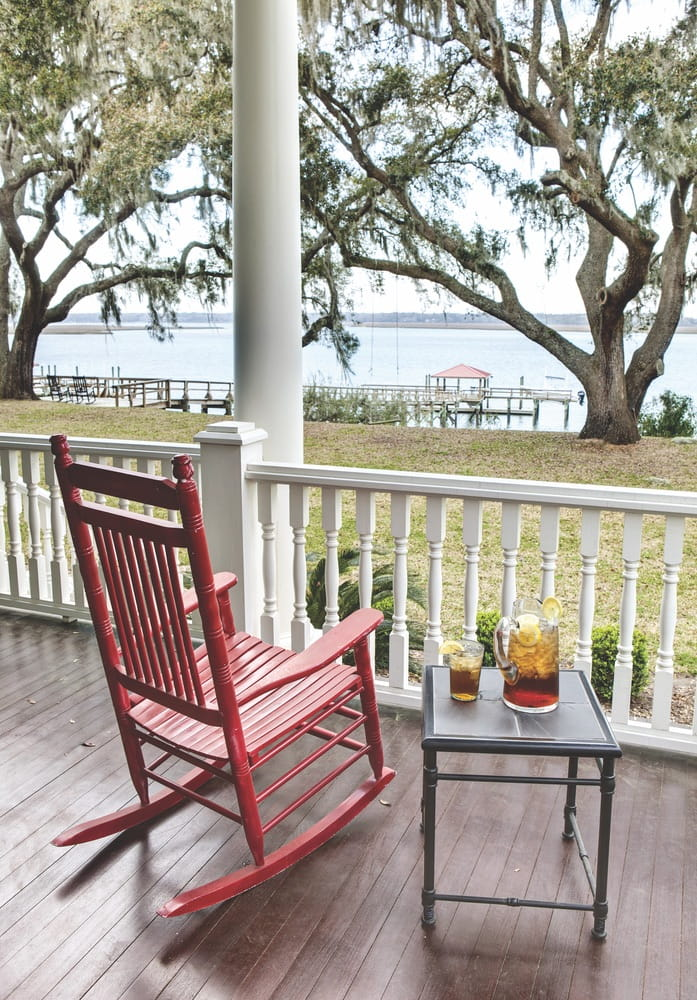 Red rocking chair and table with iced tea with waterfront view
