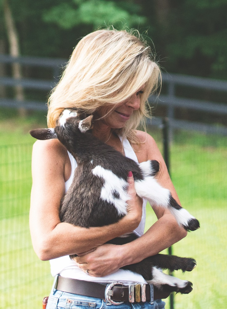 Owner Cathi Huff holding a baby goat at Atlantis Dream Farm